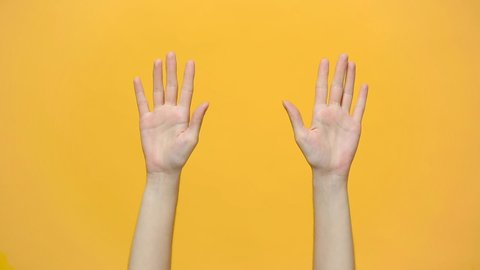 Woman hands waving, dancing snaps her fingers to music rhythm gesture isolated over yellow background in studio. Copy space for advertisement. With place for text or image. Advertising area, mock up.