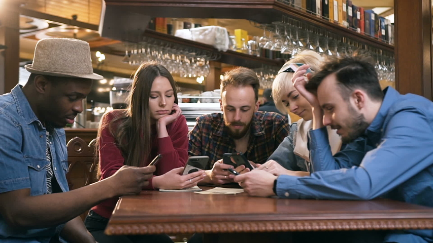 Unhappy, boring group of hipster friends using smart phone during resting in the pub, bar. | Shutterstock HD Video #1030762241
