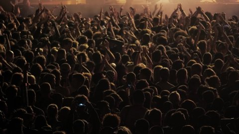 Big crowd of people dancing on music festival concert at night, street music big event applause raising hands