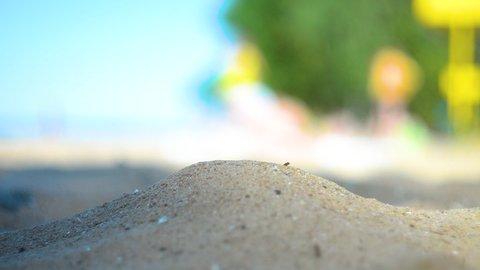 Hand closeup of releasing sand. The sand flows through the hands against a blue ocean. Summer beach vacation. Blur Background. Woman. Tan