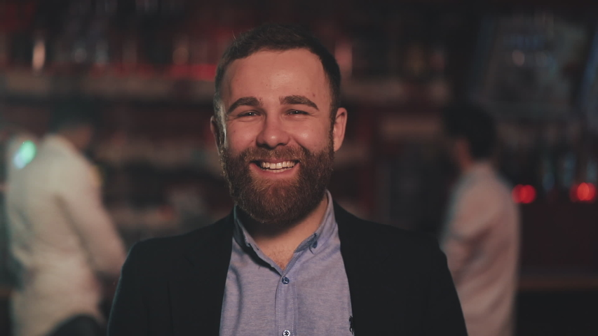 Portrait of smiling attractive man looking at camera in a bar or beer pub. Concept of youth, friendship and resting. | Shutterstock HD Video #1030856711