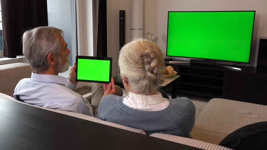 An elderly couple sits on a couch in a living room, watches TV with a green screen and looks at a tablet with a green screen | Shutterstock HD Video #1030885841