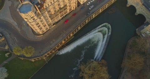Aerial tilts up from Pulteney Bridge and the Avon River to reveal historic centre of Roman city of Bath England UK at sunrise
