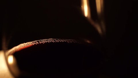 A glass of red wine in front of two burning candles. Room is only lit by the candles. Closeup, camera pan, unfocusing, pouring wine