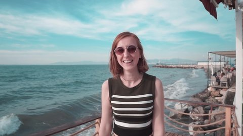 Happy attractive girl beckoning with hand gesturing and laughing on pier in summer, sunset time. Woman with sunglasses, happy, freedom, cheerful lifestyle calling, invite.