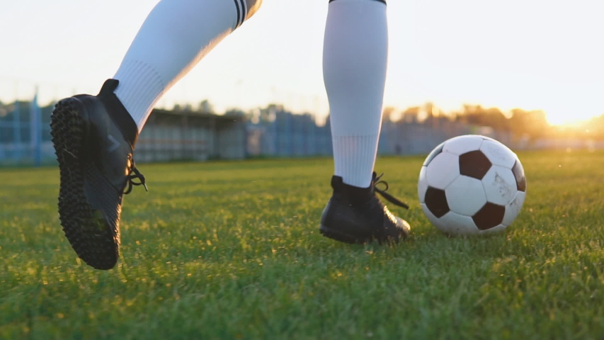 Close up of female football player running and kicking soccer ball at sunset in slow motion | Shutterstock HD Video #1030949561