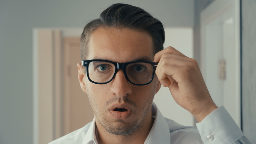 Portrait of young man is surprised and takes off his glasses in shock. He is worried about seeing | Shutterstock HD Video #1030983161