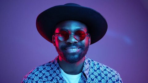 Cheerful stylish Afro American hipster man in trendy hat and stylish steampunk polarized eyeglasses attractively smiling straight to camera on bright colorful neon lights. Studio portrait. Style, new