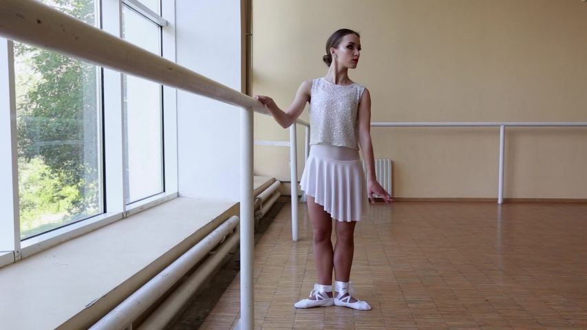 Young thin ballerina in white dress dancing near a big window. #1031006141