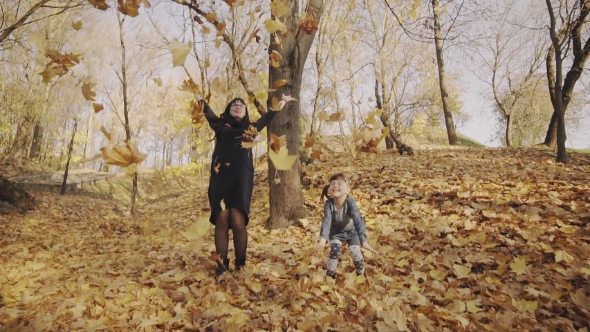 Mom and girl playing with maple leaves. Family having fun in autumn park. Mother and daughter play with autumn leaves. Full length shot