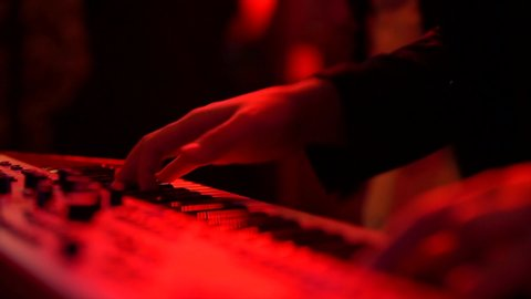 Man musician plays electronic piano at a fast pace in a nightclub under artificial light red and blue, close-up