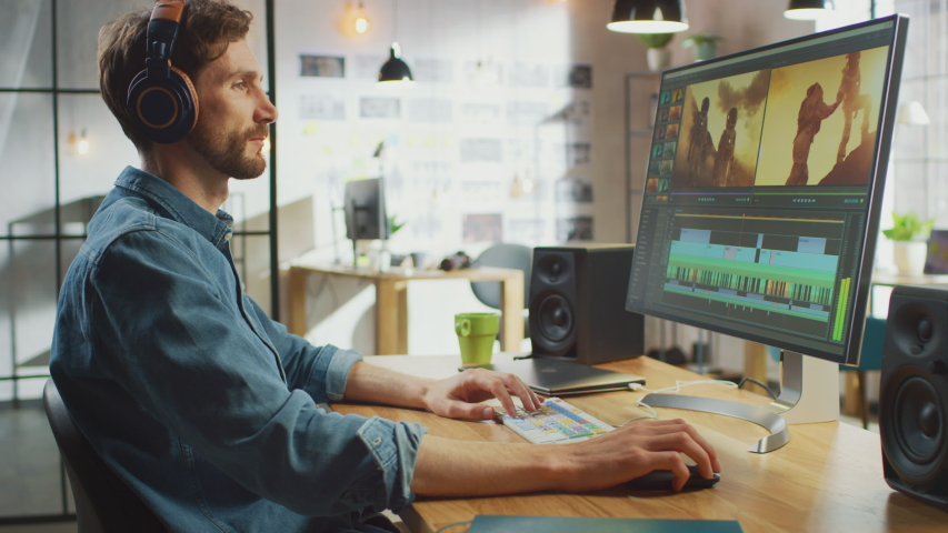 Male Video Editor Puts Headphones and Starts Working with Footage on His Personal Computer with Big Display. He Works in a Cool Office Loft. Creative Man Wears a Jeans Shirt.