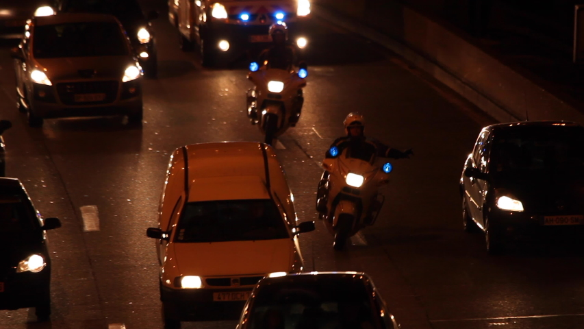 Paris, France - April 6, 2019: Motorcycle policemen and Ambulance with emergency lights flashing in Car Traffic by night at Paris. Lights, cars, fires, bus, blur effect. Lot of vehicles. Close up.