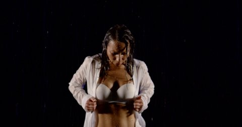 wet woman is undressing in dark room, taking off her damp shirt, drops are falling