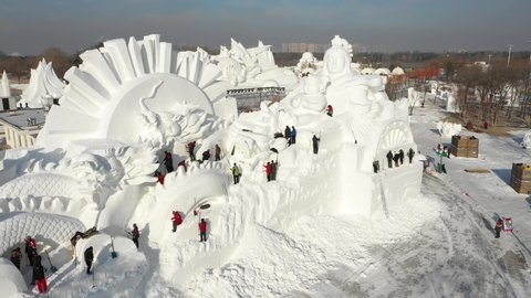 HARBIN, CHINA – JANUARY 2019: Rotating drone shot of people shoveling snow making beautiful artistic sculpture, in preparation of the Harbin ice festival in China