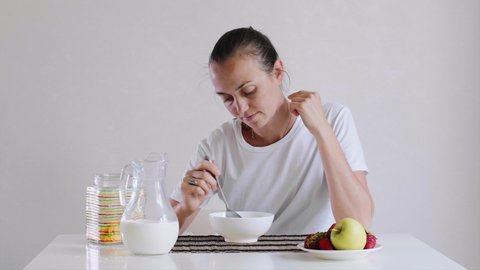 Portrait of young sunburnt woman is eating cornflakes with milk and fruits for breakfast with appetite. She is sitting at table on white background.