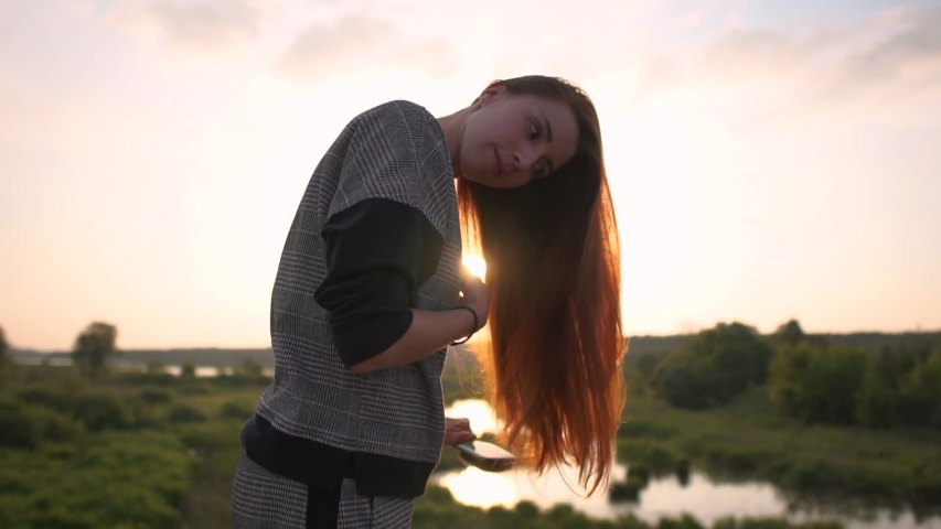 The pretty girl brushes long red hair on the nature at sunset in slow motion #1031280161