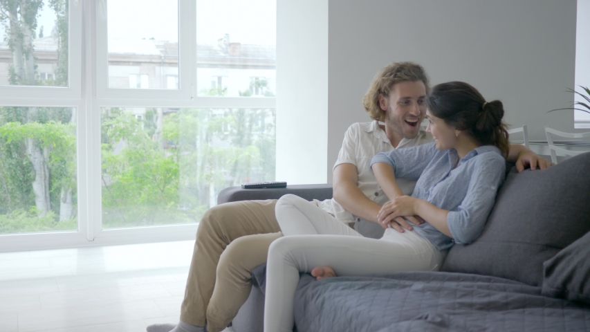Happy pregnant, young female with excitement tells male about pregnancy and puts hands on belly and future parent smiles happily sitting on couch at home | Shutterstock HD Video #1031293571