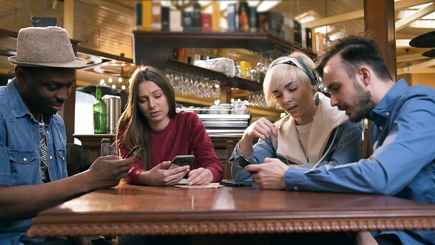 Group of stylish hipster friends using smart phone while sitting at the table in the pub, bar. Dolly shot. | Shutterstock HD Video #1031304791