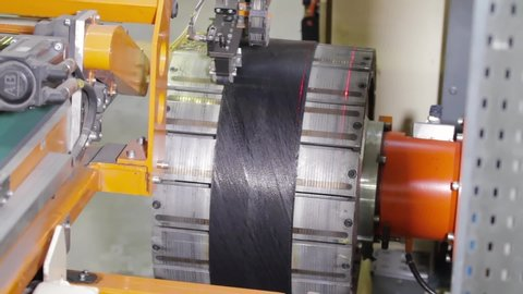 Tire manufacture robotic equipment on tire building plant at works. The rubber tape is reeled up on a drum in the machine. Tire production machine close up. Manufacture of tires.