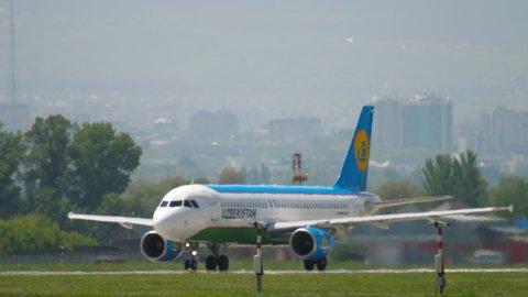 ALMATY, KAZAKHSTAN - MAY 5, 2019: Uzbekistan Airlines Airbus A320 before departure against Almaty city skyline. Almaty International Airport, Kazakhstan