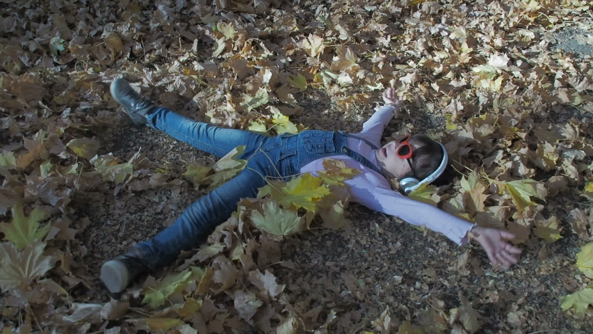 Kid playing snow angel among fallen leafs. Rest in autumn park. Funny child.