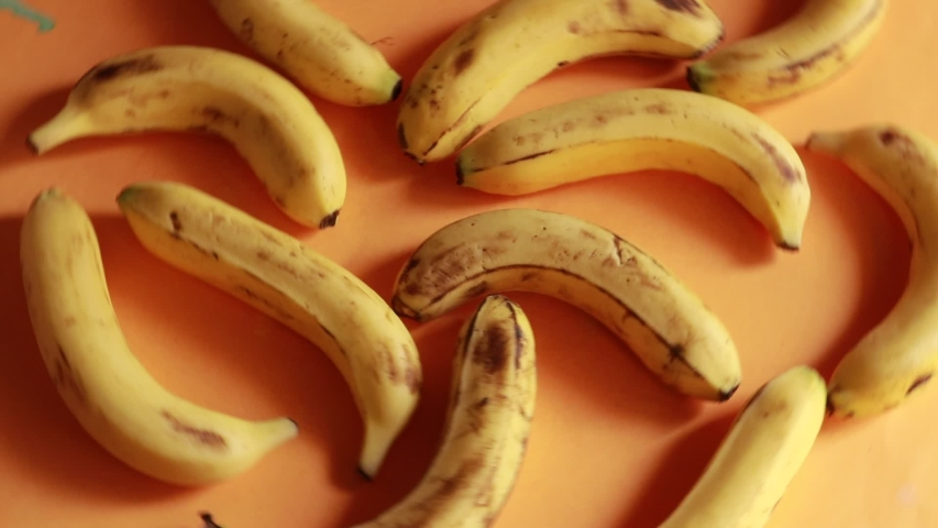 Ripe delicious wet bananas rotate clockwise on a black plate on a yellow background   Shutterstock HD Video #1031417051