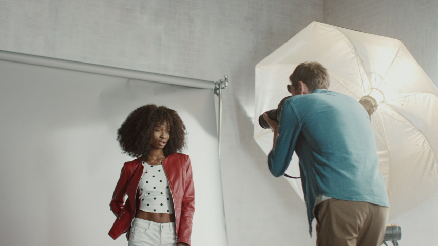 Backstage of the Photo Shoot: Make-up Artist Applies Makeup on Beautiful Black Model, in a Moment Photographer Starts Taking Photos with Professional Camera. Fashion Magazine Studio Photoshoot | Shutterstock HD Video #1031450021