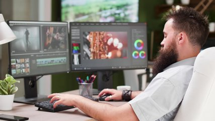 Bearded guy work as video editor or colorist in creative media agency. In the background - modern office with big TV displaying footage