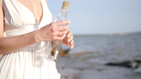 The girl puts her desire in the bottle and lets go into the sea. Bottle on the beach. More videos from this series in my portfolio