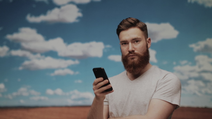 Red haired man,using his smartphone on the field and looking at the camera. Outdoor shot on a sunny day | Shutterstock HD Video #1031560991