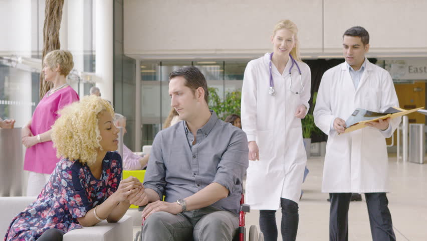 4K Caring medical staff talking to patient in a wheelchair in busy modern hospital | Shutterstock HD Video #10316495
