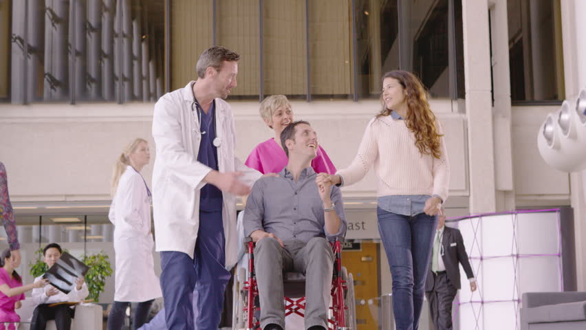 4K Caring medical staff assisting patient in a wheelchair in busy modern hospital | Shutterstock HD Video #10316924