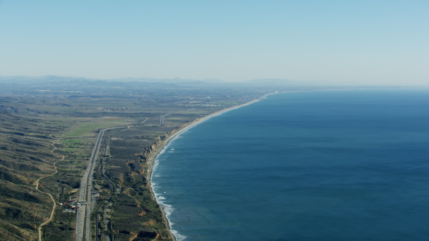 Aerial view of Pacific ocean coastline sweeping beaches Los Angeles to San Diego Highway US1 Toll road Amtrak Railroad California America RED WEAPON | Shutterstock HD Video #1031759771