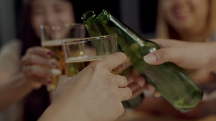 Group of young Asian friends toasting beers and laughing with snack and bottles of drink celebrating in home. Happy teen friends listening to music at summer night party celebration. Slow motion shot. | Shutterstock HD Video #1031771051