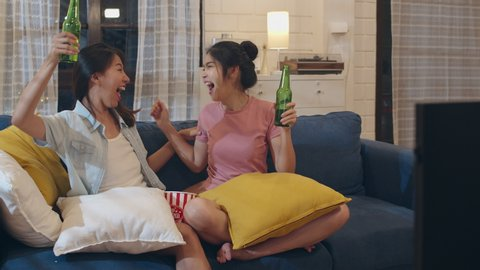Lesbian lgbt women couple party at home, Asian female drinking beer watching TV cheer soccer funny moment together on sofa in living room in night. Young lover football fan, celebrate holiday concept.