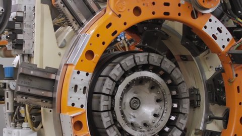 Tire manufacture robotic equipment on tire building plant at works. Tire production machine close up. Rolling drum forming tire machine in action at car tires plant. Tires production plant.