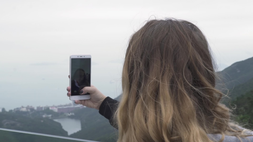 Happy travel woman taking selfie photo on mobile phone on Peak Victoria in Hong Kong city, China. Tourist girl doing selfie portrait to smart phone while vacation in Hong Kong city. Travel concept | Shutterstock HD Video #1031774651
