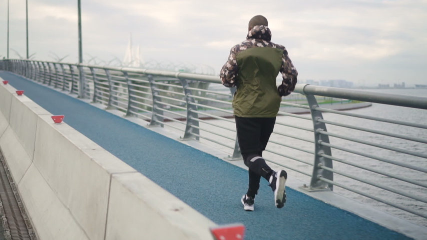 Athlete man run training air workout on river road in awesome landscape world. generous active man work unconscious for marathon trial external in summer. | Shutterstock HD Video #1031812451