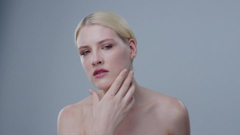 Sensual young woman doing facial massage routine for healthy glowing skin looking in the mirror. Portrait of blonde girl touching her face after spa procedures against grey background.