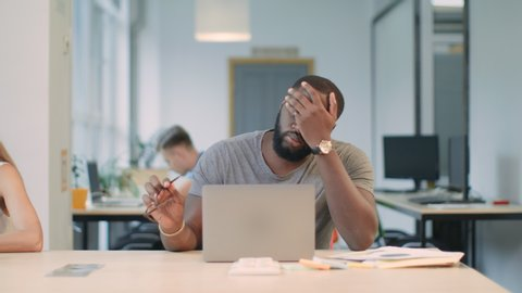 Upset man reading bad news on laptop computer at coworking space. Serious afro man stressed at office workplace. African male professional making mistake working on laptop in office.
