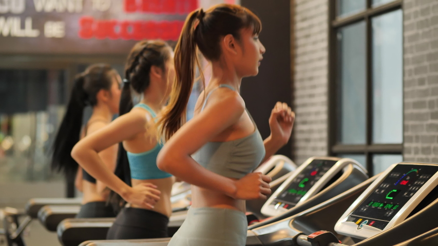 Group Young beautiful woman asian running on a treadmill at gym. Fitness and healthy lifestyle concept. Side view of girl in sportswear jogging exercise. Slow motion #1031891591