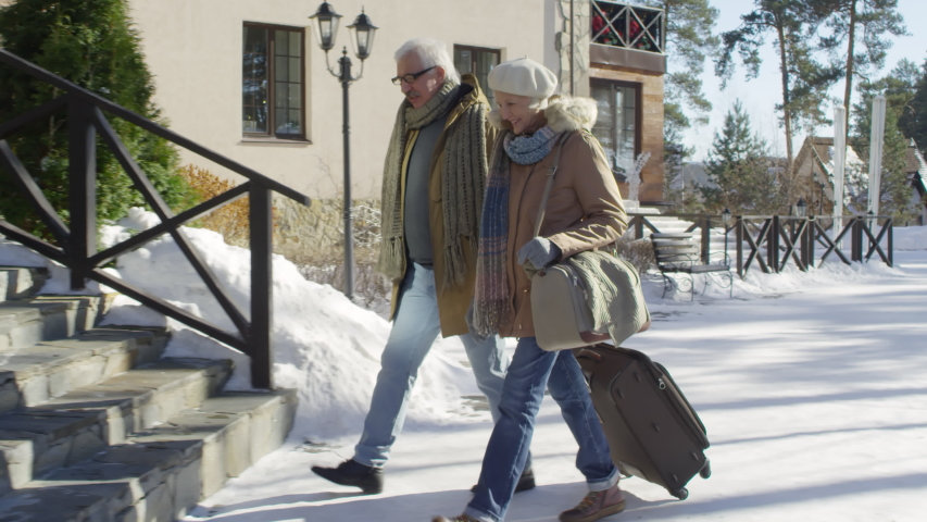 Full follow shot of happy Caucasian elderly married couple with suitcase arriving at countryside nature resort for relaxing weekend minibreak in winter, chatting and smiling, then climbing up steps #1031892011