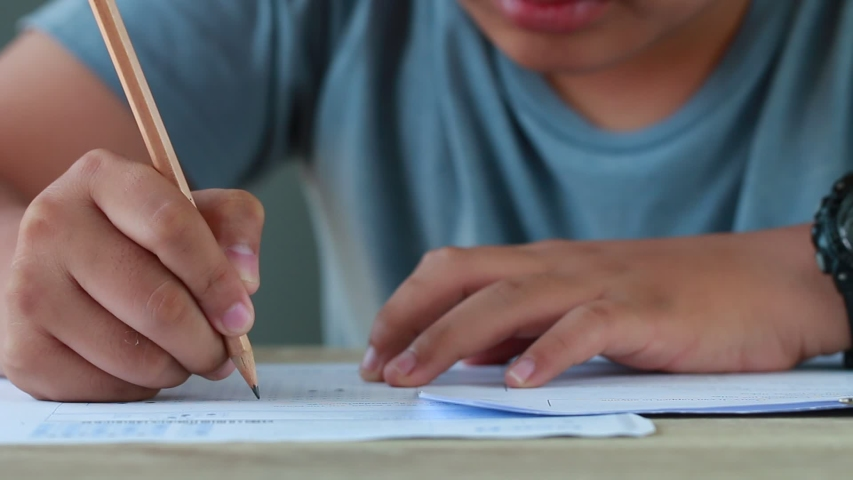 Education test in university or high school concept : Hands student holding pencil for testing exams on answer sheet, taking fill in exam document paper at campus classroom. Knowledge learning concept   Shutterstock HD Video #1031906531