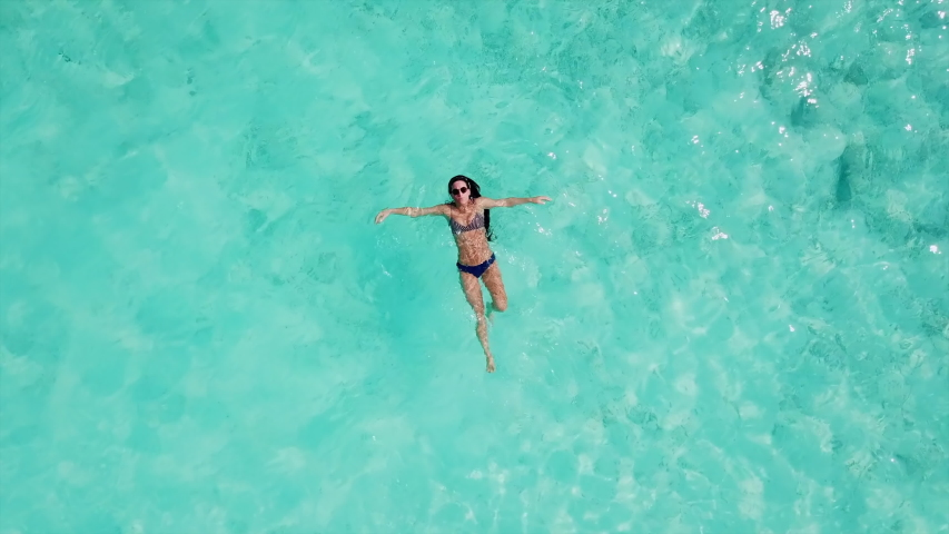 Aerial: Rising Shot from Young Woman Floating in Water to Expanse of Tropical Sea - Vabbinfaru, Maldives | Shutterstock HD Video #1031959541