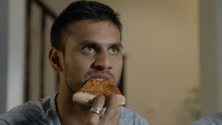 Close up of young man sitting on a sofa watching tv, eating a slice of takeaway pizza | Shutterstock HD Video #1031979821