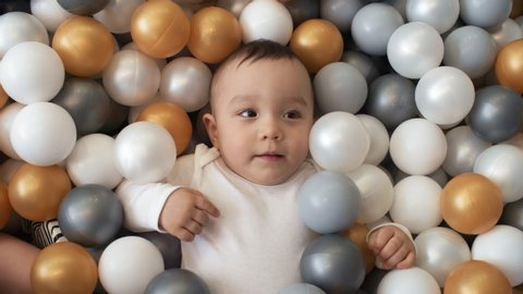 Chest-up shot of thrilled Asian baby, dressed in white bodysuit, lying on back in stylish ball pond, surrounded with grey, white and golden balls, looking at someone and laughing with delight