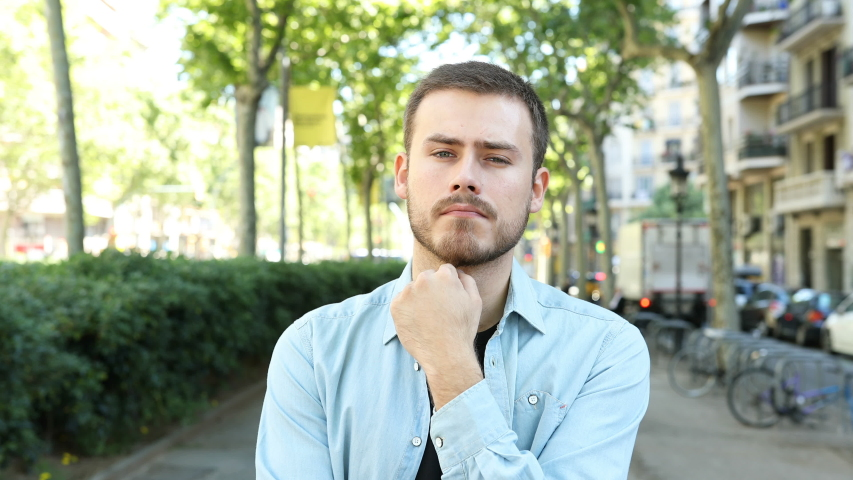 Front view of a suspicious man listening to you doubting in the street | Shutterstock HD Video #1032083021