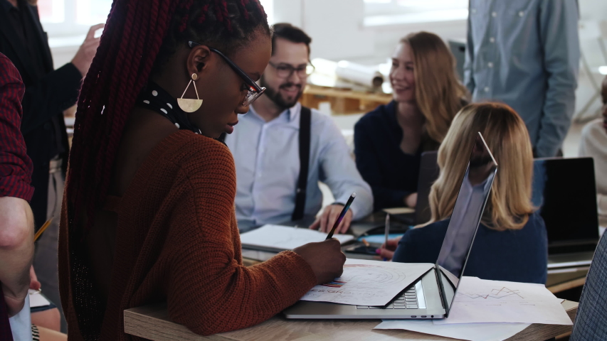 Beautiful African young woman works with documents on laptop, happy multiethnic business people in office background. | Shutterstock HD Video #1032099431