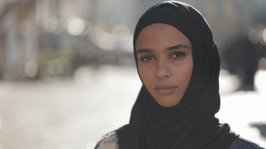 Portrait of beautiful young Muslim woman wearing hijab headscarf looking into the camera standing on the old city background. | Shutterstock HD Video #1032188981